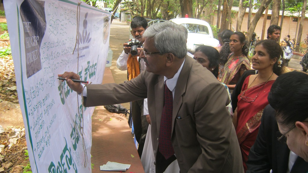 Mr. Mohan Sripadha Sankoli, Principal District Judge of Mysore, imprinting his signature Violence against women